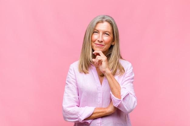 Ładna kobieta w średnim wieku, wyglądająca na szczęśliwą i uśmiechniętą z ręką na brodzie, zastanawiająca się lub zadająca pytanie, porównująca opcje