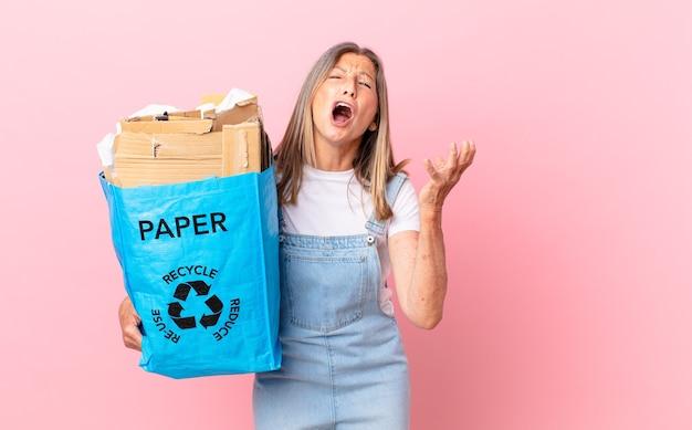 Ładna kobieta w średnim wieku wyglądająca na zdesperowaną, sfrustrowaną i zestresowaną koncepcję recyklingu kartonu
