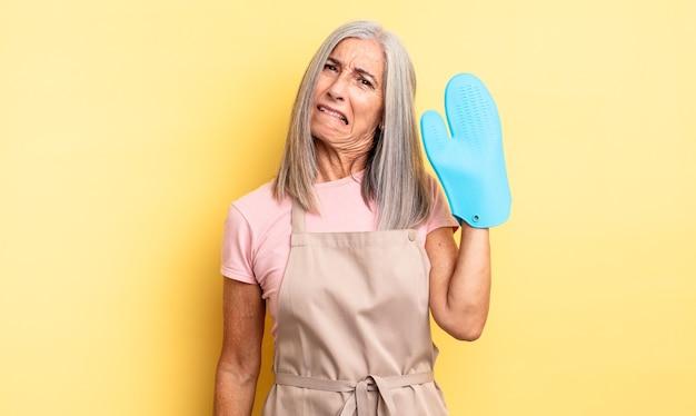 Ładna kobieta w średnim wieku wyglądająca na zdziwioną i zdezorientowaną. koncepcja rękawic kuchennych