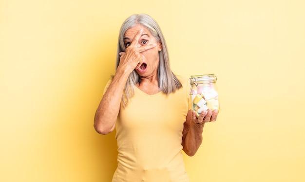 Ładna kobieta w średnim wieku wyglądająca na zszokowaną, przestraszoną lub przerażoną, zakrywająca twarz dłonią. koncepcja butelki cukierków