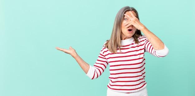 Ładna kobieta w średnim wieku wyglądająca na zszokowaną, przestraszoną lub przerażoną, zakrywająca twarz dłonią