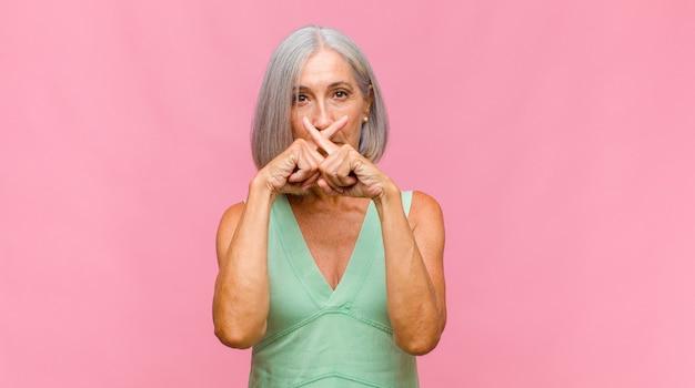 Ładna kobieta w średnim wieku, wyglądająca poważnie i krzywo, z palcem przyciśniętym do ust, domagająca się ciszy lub spokoju, zachowywania tajemnicy