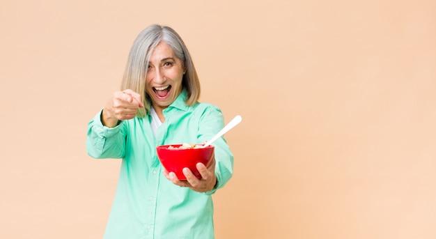 Ładna kobieta w średnim wieku z miską śniadaniową