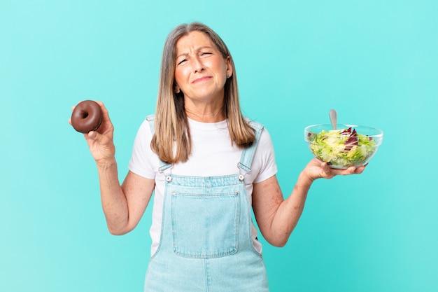 Ładna kobieta w średnim wieku z pączkiem i sałatką. koncepcja diety