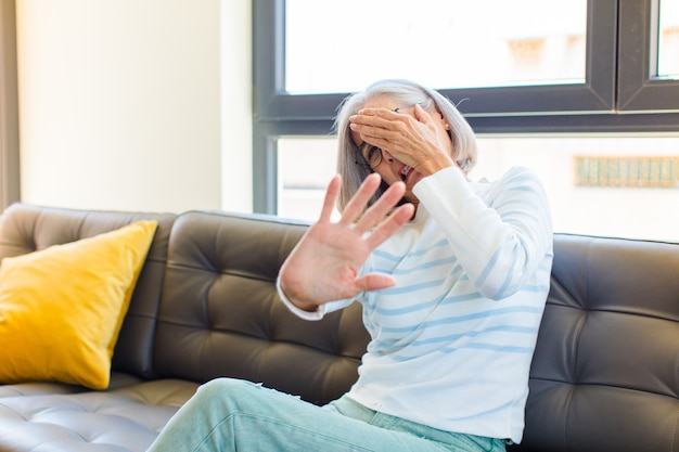 Ładna kobieta w średnim wieku zakrywająca twarz ręką i wyciągająca drugą rękę do przodu, aby zatrzymać się do przodu, odmawiając zdjęć lub zdjęć