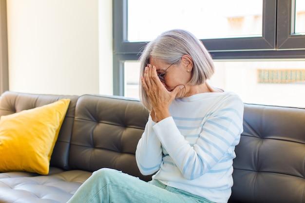 Ładna kobieta w średnim wieku zasłaniająca oczy dłońmi smutnym, sfrustrowanym spojrzeniem rozpaczy, płacz, widok z boku