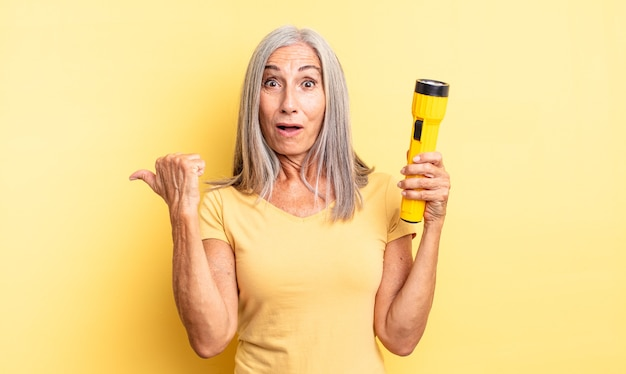 Ładna kobieta w średnim wieku, zdumiona z niedowierzaniem. koncepcja latarki