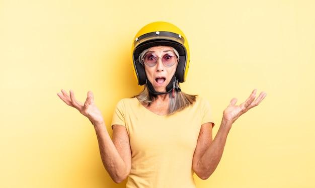 Ładna kobieta w średnim wieku zdumiona, zszokowana i zdumiona niewiarygodnym zaskoczeniem. koncepcja kasku motocyklowego