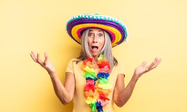 Ładna kobieta w średnim wieku zdumiona, zszokowana i zdumiona niewiarygodnym zaskoczeniem. koncepcja meksykańskiej imprezy