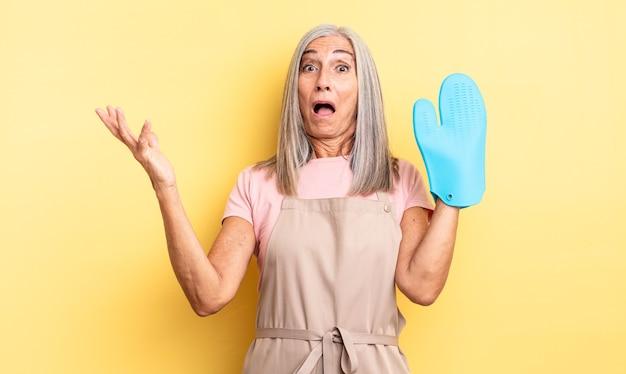 Ładna kobieta w średnim wieku zdumiona, zszokowana i zdumiona niewiarygodnym zaskoczeniem. koncepcja rękawic kuchennych