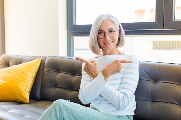 Ładna kobieta w średnim wieku, zdziwiona i zdezorientowana, niepewna i wskazująca z wątpliwościami w przeciwnych kierunkach