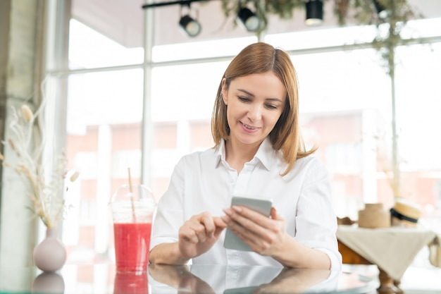 Ładna kobieta w średnim wieku ze smartfonem dokonywanie selfie w kawiarni siedząc przy stole, popijając koktajl truskawkowy i ciesząc się wolnym czasem