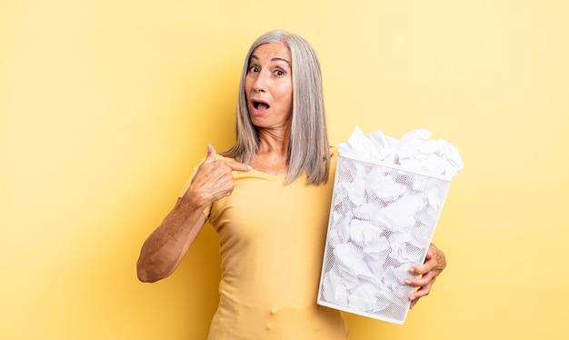 Ładna kobieta w średnim wieku, zszokowana i zaskoczona, z szeroko otwartymi ustami, wskazując na siebie. koncepcja awarii kulek papierowych