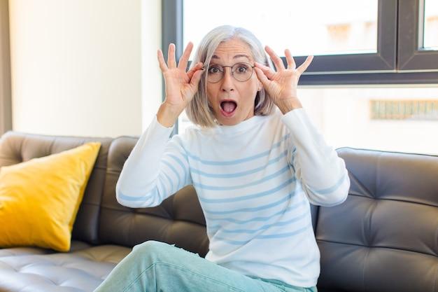 Ładna kobieta w średnim wieku, zszokowana, zdumiona i zdziwiona, trzymająca okulary ze zdumieniem i niedowierzaniem