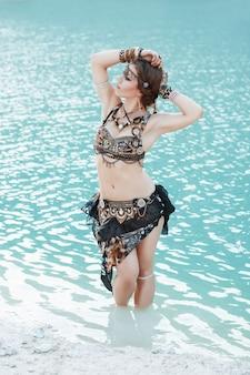 Ładna kobieta w stylu tribal na białej, piaszczystej plaży w pobliżu wody