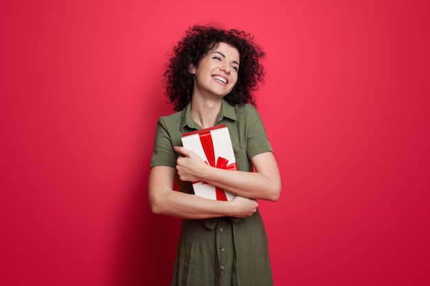 Ładna kobieta w sukience i kręconych włosach obejmująca prezent i uśmiech na czerwonej ścianie w studio