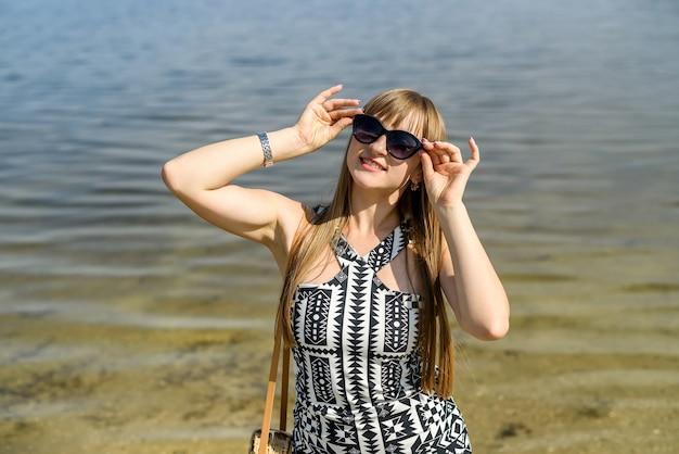 Ładna kobieta w sukience w pobliżu jeziora, czas letni