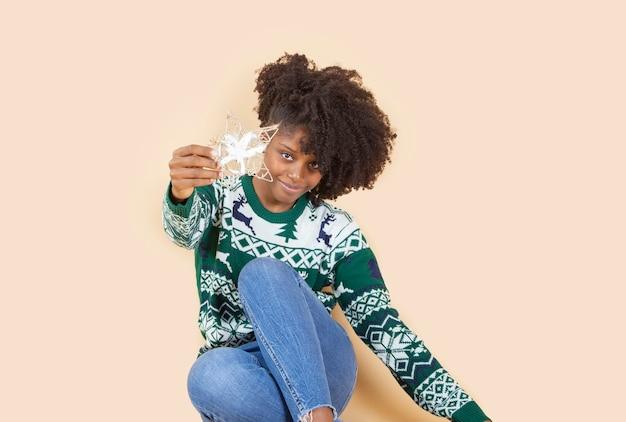 Ładna kobieta w świątecznych ubraniach i świątecznych dekoracjach, beżowe tło