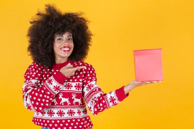 Ładna kobieta w świątecznym swetrze i prezentem w dłoniach, żółte tło