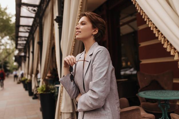 Ładna kobieta w szarym stroju pozowanie w pobliżu ulicznej kawiarni. krótkowłosa urocza dziewczyna w oversize'owej kurtce uśmiecha się i cieszy się wiosennym dniem na dworze