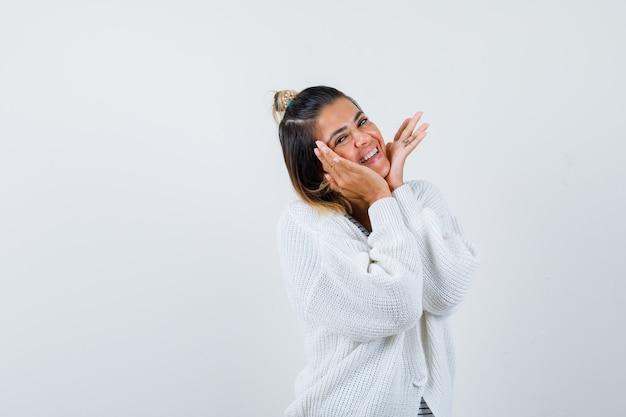Ładna kobieta w t-shircie, sweterek trzymający się za ręce pod brodą i patrzący wesoło