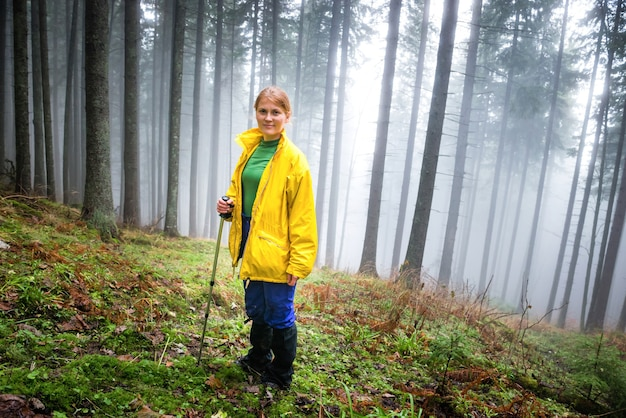 Ładna kobieta w tajemniczym lesie z mgłą