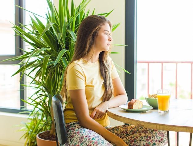 Ładna kobieta w widoku profilu chce skopiować przestrzeń do przodu, myśleć, wyobrażać sobie lub marzyć