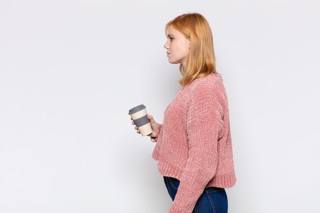 Ładna kobieta w widoku profilu, która chce skopiować przestrzeń do przodu, myśląc, wyobrażając sobie lub marząc na jawie