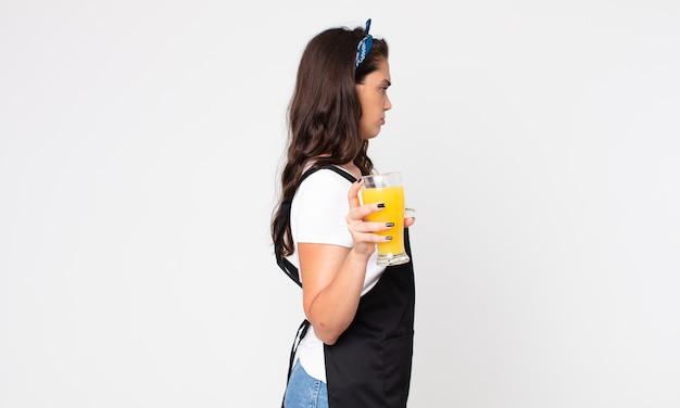 Ładna kobieta w widoku profilu myśląca, wyobrażająca sobie lub marząca na jawie i trzymająca szklankę soku pomarańczowego