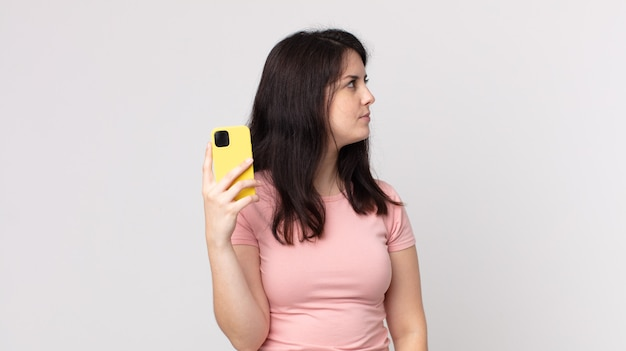 Ładna kobieta w widoku profilu myśli, wyobraża sobie lub marzy za pomocą smartfona