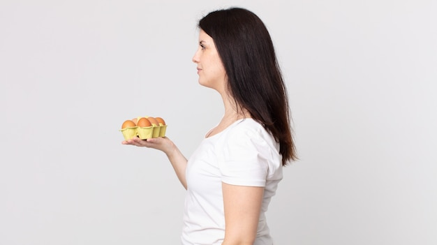 Ładna kobieta w widoku z profilu myśląca, wyobrażająca sobie lub marząca na jawie i trzymająca pudełko z jajkami