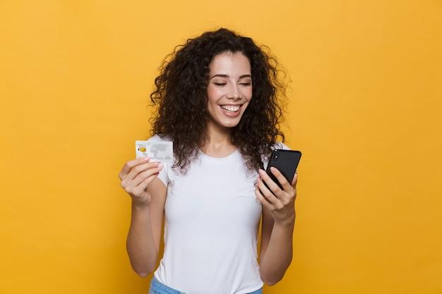 Ładna kobieta w wieku 20 lat nosząca zwykłe ubrania, trzymająca telefon komórkowy i kartę kredytową na żółto