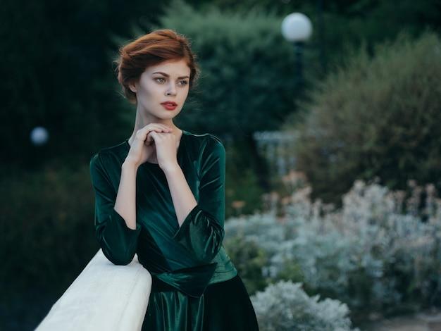 Ładna kobieta w zielonej sukience na zewnątrz w egzotycznych parkach