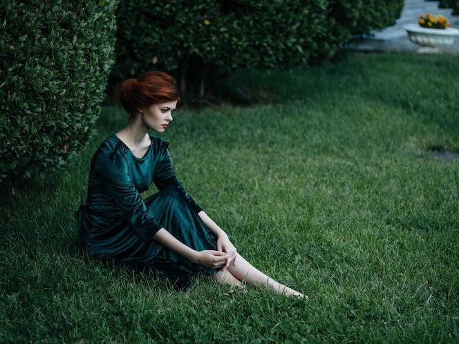 Ładna kobieta w zielonej sukience siedzi w ogrodzie letnie wakacje