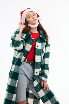 Ładna kobieta w zielonym płaszczu w kratę santa hat christmas holiday. wysokiej jakości zdjęcie