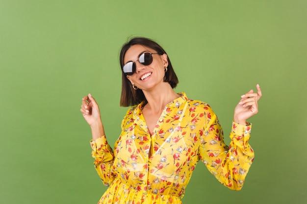 Ładna kobieta w żółtej letniej sukience i okularach przeciwsłonecznych, zielone studio, szczęśliwe pozytywne wesołe radosne emocje