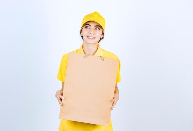 Ładna kobieta w żółtym mundurze trzyma brązową pustą papierową torbę rzemieślniczą.