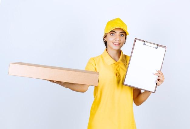 Ładna kobieta w żółtym mundurze trzyma brązowe puste pudełko papierowe rzemieślnicze z folderem.