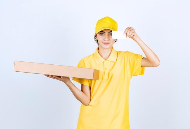 Ładna kobieta w żółtym mundurze trzyma brązowe puste pudełko z papieru rzemieślniczego.