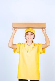 Ładna kobieta w żółtym mundurze trzymająca nad głową brązowe puste pudełko z papieru rzemieślniczego.