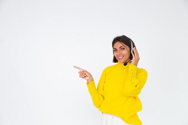 Ładna kobieta w żółtym swetrze na białym menedżerze ze słuchawkami szczęśliwy uśmiech wskazujący palec w lewo