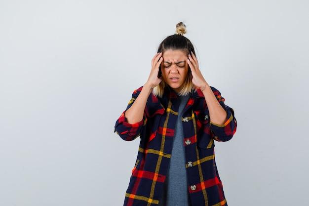 Ładna kobieta w zwykłych ubraniach cierpi na migrenę i wygląda na zirytowaną