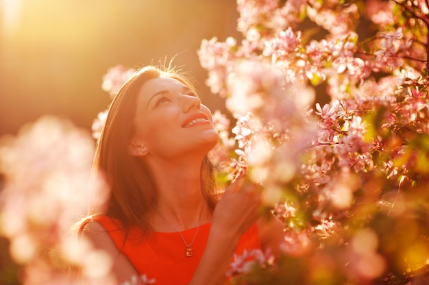 Ładna kobieta wącha kwitnącej jabłoni w lato ogródzie