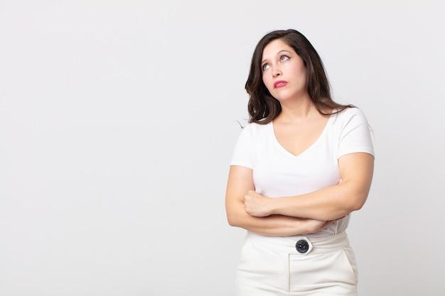 Ładna kobieta wątpi lub myśli, przygryza wargę i czuje się niepewnie i zdenerwowana, chcąc skopiować przestrzeń z boku