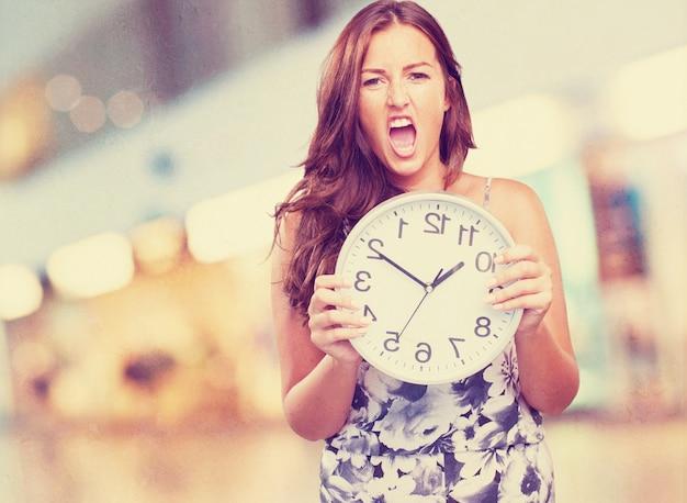 Ładna kobieta wściekły gospodarstwa zegar