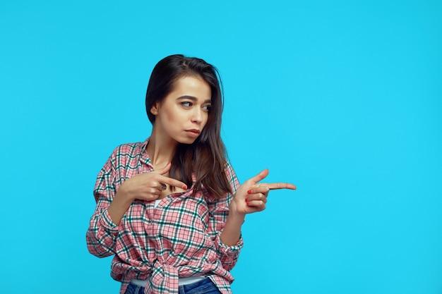 Ładna kobieta, wskazując na prawo puste miejsce na białym tle nad niebieską ścianą