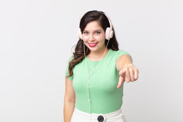 Ładna kobieta wskazująca na kamerę, która wybiera cię do słuchania muzyki przez słuchawki