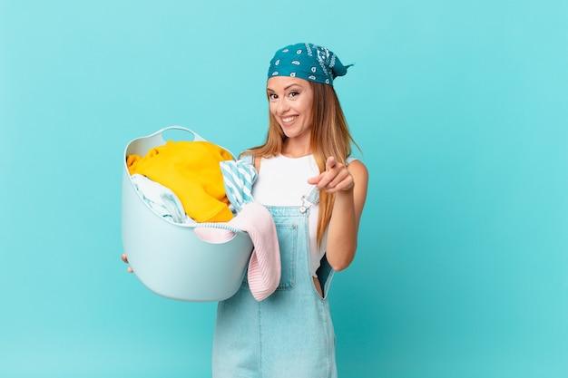Ładna kobieta wskazująca na kamerę, która wybiera cię, trzymając kosz do prania