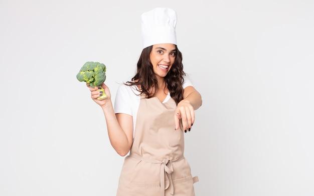 Ładna kobieta wskazująca na kamerę, która wybiera cię w fartuchu i trzyma brokuły
