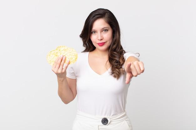Ładna kobieta wskazująca na kamerę wybierającą cię i trzymająca dietetyczne ciastka ryżowe